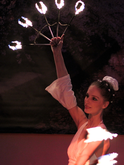 Feuertänzerin mit Feuerfächern in weissem Kostüm