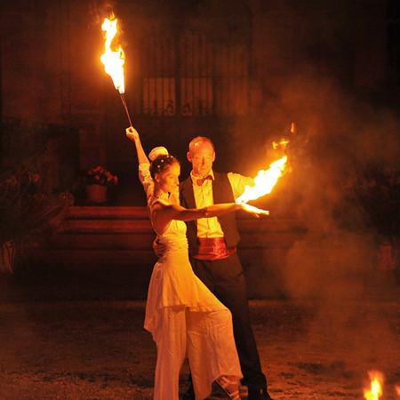 Feuerartisten Paar zieht Flammen über den Arm bei Feuershow für Hochzeit