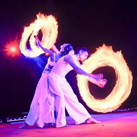 Feuerartistenpaar mit Feuerpoi in weissen Kostümen bei Bühnenshow