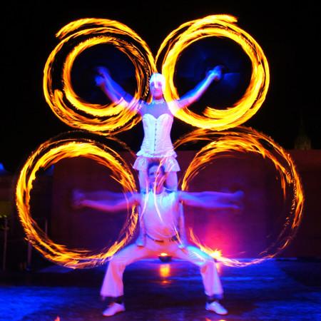 Feuerartisten Paar mit Flammenspiralen blau beleuchtet bei Feuershow