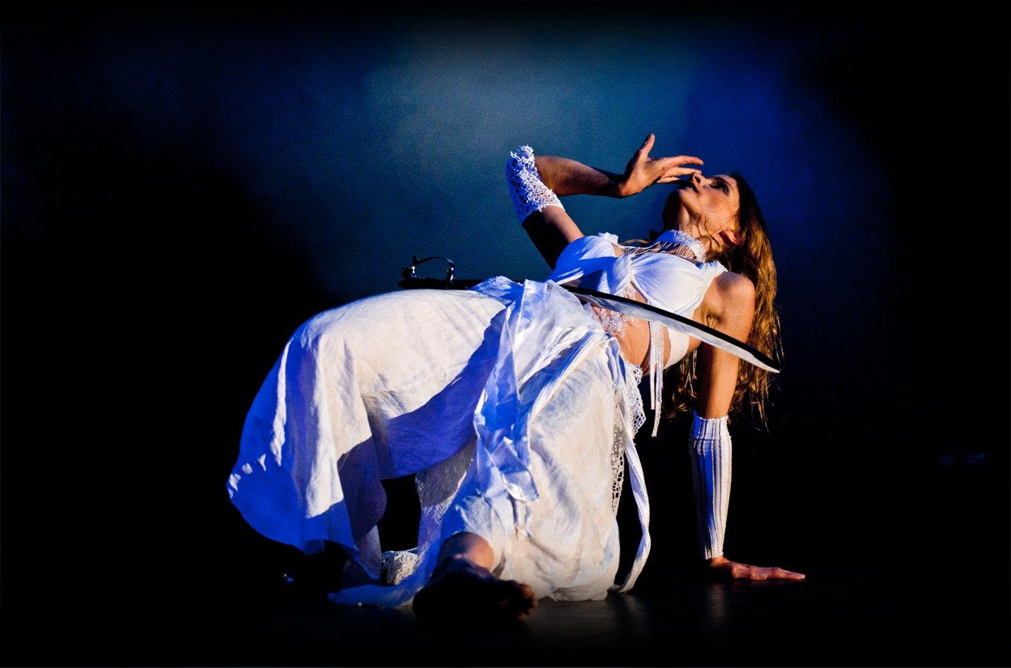 Orientalische Tänzerin balanciert Säbel auf Bauch mit weissem Kostüm