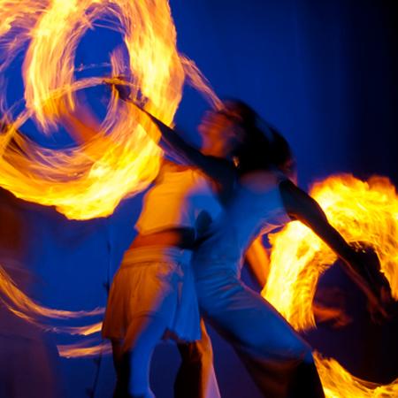 Ein Feuerkünstler Paar spielt Rücken an Rücken Poi