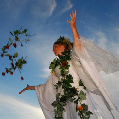 Stelzenläuferin in weissem Kostüm mit Efeuranken wirft rote Rosen