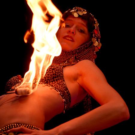 Orientalische Tänzerin zieht Feuerflammen über ihren Bauch