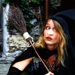 Frau in mittelalterlichem Hexenkostüm mit Besen